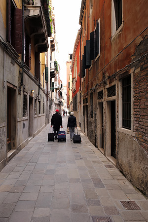 townscape: Venice, Italy - September 22, 2015: back view of senior couple man and woman walks and rolls suitcases wheeled travel bags trolley cases along narrow street on townscape background, vertical picture