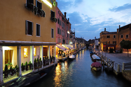 townscape: Venice, Italy - September 22, 2015: night view of venetian canal with beautiful illumination and boats at moorings in sea water on townscape background, horizontal picture Editorial