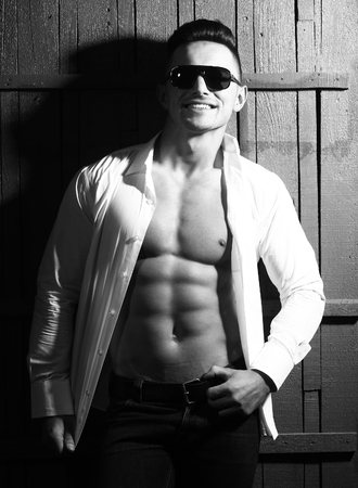 unbutton: Glamour gorgeous happy smiling sexy young guy man with athletic muscular torso in trendy sunglasses dressd in unbutton shirt and dark trousers leaning on wooden wall black and white studio, vertical