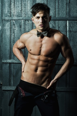 half naked: Handsome young sexy man brunet with naked muscular athletictorso dark bow tie on neck waering black underwear and unbutton trousers looking straight posing on gray wooden background, vertical photo Stock Photo