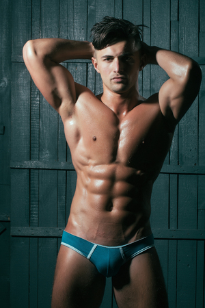 nackter junge: Gorgeous young sexy muscular bodybuilder man with cool pectorals  abdominal muscles and biceps looking straight wearing in blue underwear posing with hands behind head on dark background, vertical