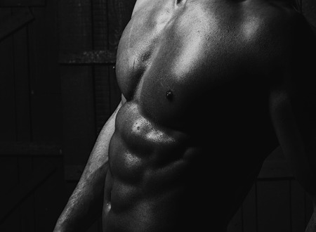 naked black men: Black and white closeup of beautiful male muscular naked torso with strong breast sporting perfect pectorals and abs muscles studio on dark background, horizontal picture Stock Photo