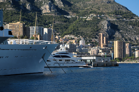 ocean liner: Monte Carlo, Monaco - September 20, 2015: white ocean liner and yacht modern vessels at moorage in sea port on sunny summer day against mountains on cityscape background, horizontal picture Editorial