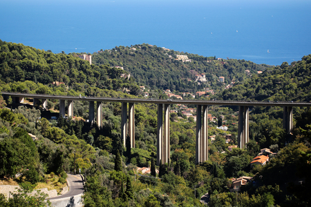 monte carlo: Monte Carlo, Monaco - September 20, 2015: modern tall highway fixed bridge over mixed green forest mountain landscape on bright blue sea background, horizontal picture Editorial