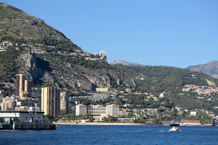 Monte Carlo, Monaco - September 20, 2015: view from sea on town resort situates on seaside below hillsides mountains against bright blue sky on seascape background, horizontal picture Editorial