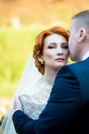 red haired: Wedding romantic couple of young red haired bride in white dress kissing with bridegroom outdoor on natural background, verical picture Stock Photo