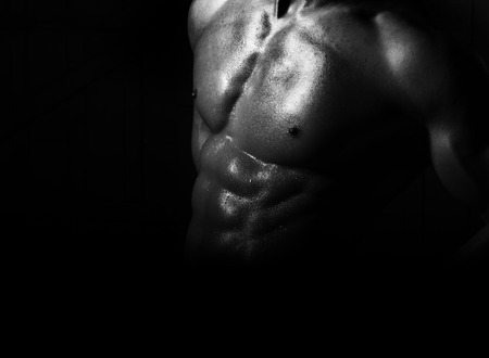 bare breast: Gorgeous muscular naked sexy shining male torso with strong athletic chest and berfect pectoral and abdominal muscles on sporting belly black and white on dark background studio closeup, horizontal Stock Photo