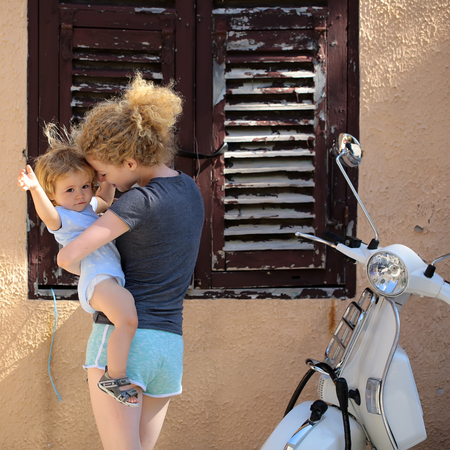 motor bike: Young beautiful blonde woman holding little baby boy child in hands standing near house with brown window and white motor bike urban transportation sunny day outdoor, square picture