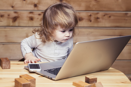 Cute funny little baby boy with long blonde curly hair playing on computer and mobile phone near toy building blocks indoor on wooden background, horizontal picture 免版税图像