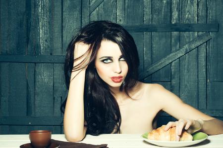donna nuda: Sensuale attraente donna in topless con i capelli lunghi bruna e trucco luminoso seduto con colazione a base di caffè e grande hamburger su fondo in legno, immagine orizzontale Archivio Fotografico