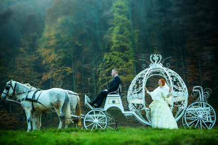 Young wedding romantic couple of bride in white dress and bridegroom in suit in cinderella carriage with horses in deep green forest outdoor on natural background, horizontal picture