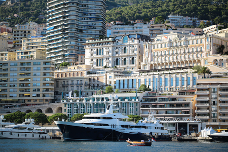 inshore: Monte Carlo, Monaco - September 20, 2015:  yachts luxury large vessels ships at moorage in port and small motor boat inshore on sunny summer day on cityscape background, horizontal picture Editorial