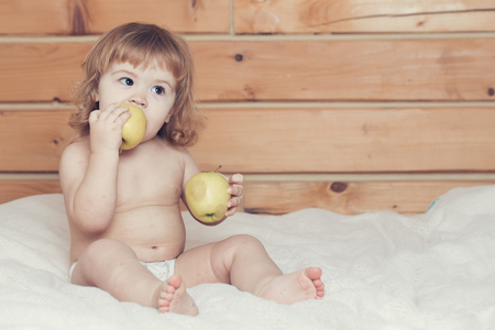 boy  naked: Cute happy beautiful smiling playful child boy with wet hair sitting in hothouse bath white fluffy towel naked indoor on wooden background eating apples, horizontal picture