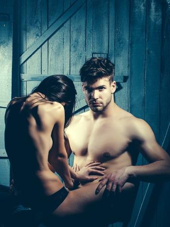 seins nus: Jeune couple sensuel de l'homme musclé macho avec torse nu et sexy femme aux seins nus avec le dos assis sur amant intérieur sur fond de bois, l'image verticale