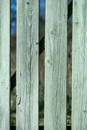 boarded: Distant boarded fence old wooden palisade wood boards with knots faded blue paint closeup on timber background Stock Photo
