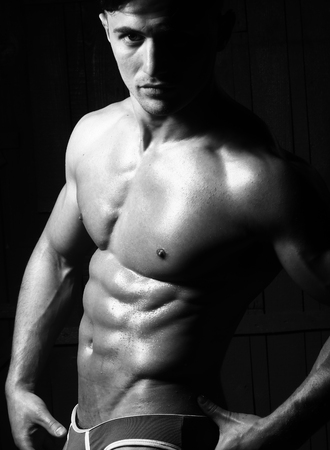 bare breast: Iron sexy beautiful man with muscular athletic bare torso perfect abdominal and six-pack muscles strong chest in underpants looking straight poising on dark backdrop studio black and white closeup