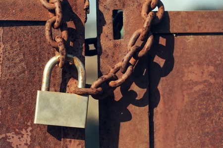 metal gate: Padlock with shackle and locking mechanism closeup one portable lock on chain on unpainted rusty metal gate doors outdoor on blurred background Stock Photo