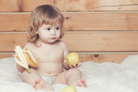 naked child: Cute happy beautiful smiling playful child boy with wet hair sitting in hothouse bath white fluffy towel naked indoor on wooden background eating banana and apple, horizontal picture Stock Photo
