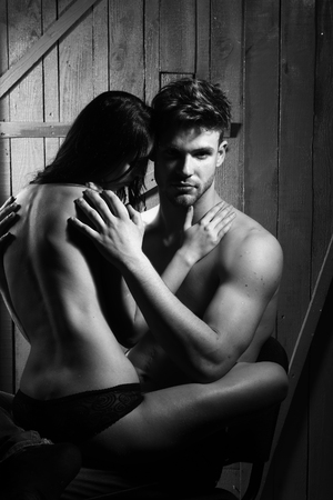 sexy topless woman: Young sensual couple of muscular macho man with bare torso and pretty sexy topless woman with back sitting on lover indoor on wooden background black and white, vertical picture Stock Photo