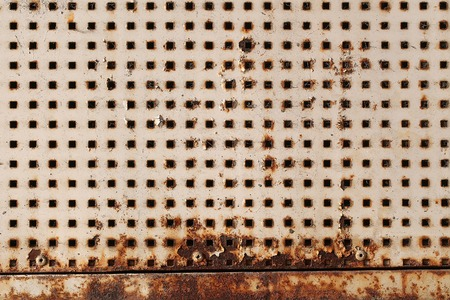 Plate metallic rusty with square holes slots perforated sheet shield screen on metal background
