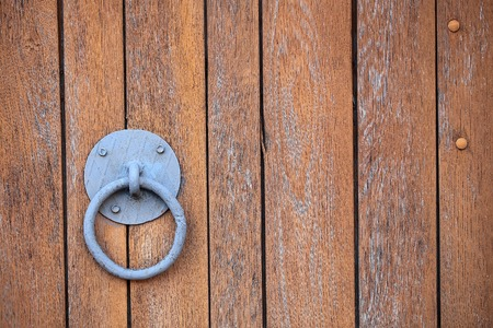 wicket door: Door knocker metal ring and plate on old aged wooden brown painted fence gate door palisade on timber background
