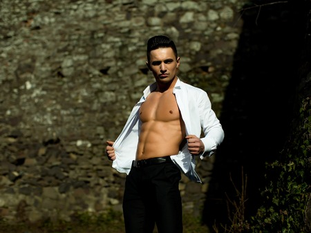 Man bare-chested young handsome sensual model in white shirt gaped open and black trousers looks at camera poses outside on masonry background