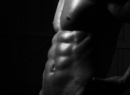 naked abs: Closeup of male cool strong naked abdomen with strong abs and 6 pack muscles and beautiful strong topless breast of sexy young man athlete closeup black and white studio on dark background