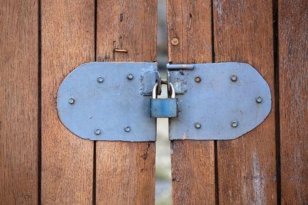 locking: Padlock small portable lock with shackle and locking mechanism on old aged wooden brown painted fence gate palisade on timber background