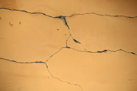 fractures: Cracked plaster wall orange splits fractures on surface layer cover aged look on concrete background Stock Photo