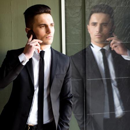 conversaciones: El hombre joven modelo sensual elegante hermoso en juego con la corbata flaca conversaciones de escudo abierto en el tel�fono m�vil se ve lejos mano en el bolsillo refleja en el espejo sobre fondo gris