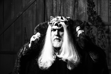 metaphysics: Bearded senior man in long white wig vine crown as Zeus god in fur coat indoor on wooden background Stock Photo