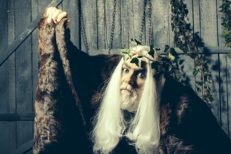 manteau de fourrure: homme �g� Bearded en blanc longue couronne de vigne perruque comme dieu Zeus en manteau de fourrure int�rieure sur fond de bois Banque d'images