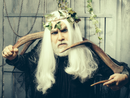 metaphysics: Bearded senior strange mysterious man wizard in long white wig vine crown as Zeus god with big animal horns indoor on wooden background Stock Photo