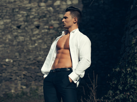 trouser: Man half face bare-chested young handsome sensual model in white shirt gaped open poses with hands in black trouser pockets outside on masonry background