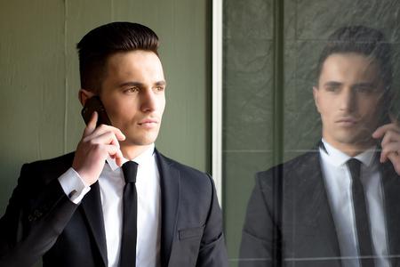conversaciones: El hombre joven modelo sensual elegante hermoso en juego con la corbata flaca conversaciones de escudo abierto en el teléfono móvil se ve lejos mano en el bolsillo del retrato refleja en el espejo sobre fondo gris