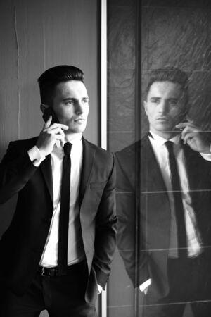 conversaciones: El hombre joven modelo sensual elegante hermoso en juego con la corbata flaca conversaciones de escudo abierto en el teléfono móvil se ve lejos mano en el bolsillo refleja en el espejo blanco y negro sobre fondo gris