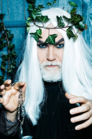 metaphysics: Bearded senior strange mysterious man wizard in long white wig vine crown as Zeus god with medallion on chain indoor on wooden background Stock Photo