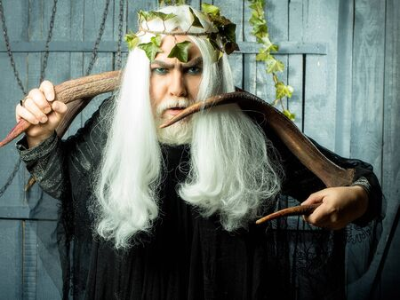 enchant: Bearded senior strange mysterious man wizard in long white wig vine crown as Zeus god with big animal horns indoor on wooden background Stock Photo