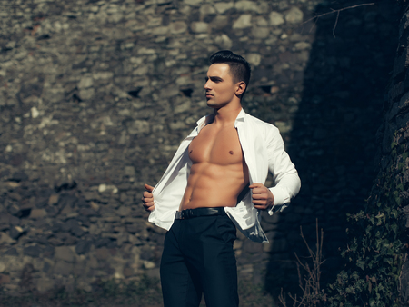 barechested: Man half face bare-chested young handsome sensual model in white shirt gaped open and black trousers poses outside grey color filtre on masonry background