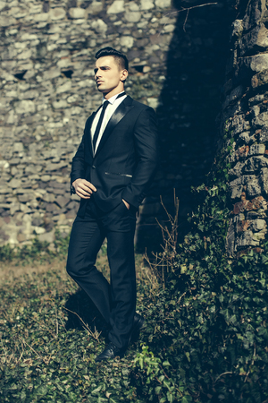 trouser legs: Man half face young handsome elegant model in suit with skinny necktie poses with hand in trouser pocket one leg backward outdoor on masonry background Stock Photo