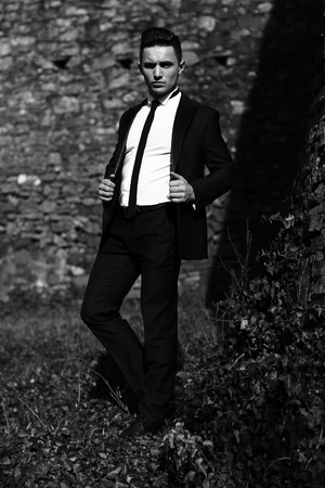 unbutton: Man young handsome elegant model in unbutton suit coat with skinny necktie poses one leg backward looks in camera outdoor black and white on masonry background