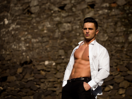 trouser: Man bare-chested young handsome sensual model in white shirt gaped open poses with hands in black trouser pockets outside on masonry background
