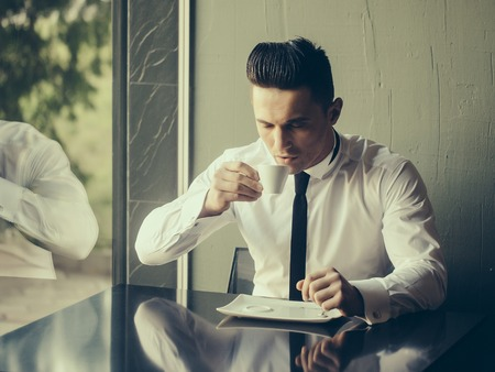 wears: Man young handsome elegant model wears white shirt black skinny necktie sits at table drinks coffee reflects in glass window and looks in cup indoor on grey background