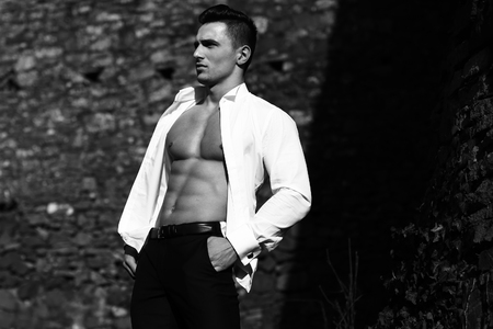 barechested: Man  young handsome sensual model in shirt gaped open poses with hand in trousers pocket  on masonry background, black and white
