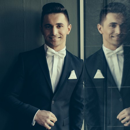 Man in suit with white handkerchief and bow tie young elegant stylish stands smiles and reflects in mirror on grey background