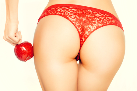 nude female buttocks: Female buttocks of young woman in panties with red apple isolated on white Stock Photo