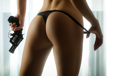 Female with sexy buttocks with a gun. Criminal and dangerous. Stock Photo