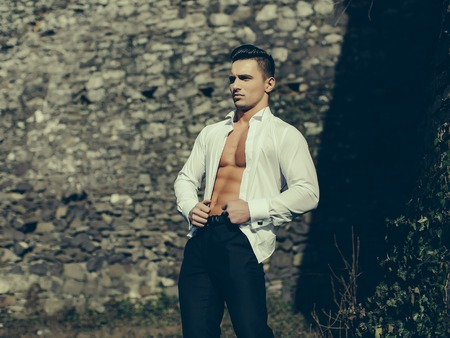 barechested: Man half face bare-chested young handsome sensual model in white shirt gaped open poses hands on waist and black trousers outside grey color filtre on masonry background