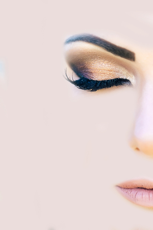 Closeupfemale face with fashion visage. Dark brown eyes makeup and long eyelashes. Evening style. Beaige mesh background, copy space
