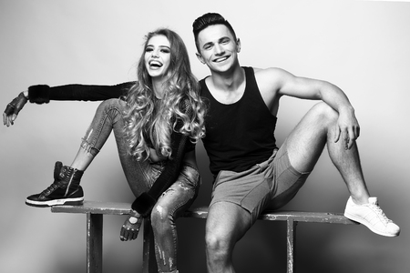 sexi: Young couple sitting in studio. Beauty and fashion, friends, black and white